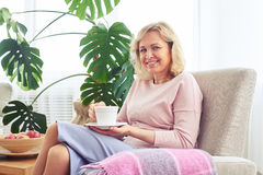Nette erwachsene Frau, die Rest mit Tasse Kaffee im Lehnsessel achtern hat Lizenzfreies Stockbild