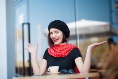Nette erwachsene Frau im Café mit den Händen auseinander stockfotos