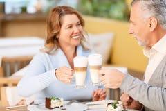 Nette erwachsene Paare, die im Café sitzen stockfotografie