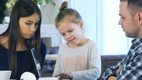 Nette europäische Familie, die im Laptop schaut und etwas lächelt während ihrer Freizeit im Café bespricht stockfotos