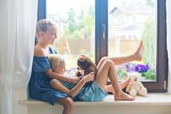 Nette europäische Schwestern, die mit Spielwaren auf Schwelle nahe Fenster spielen stockfoto