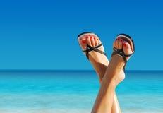 Füße gekreuzt auf einem Inselparadies Stockbild