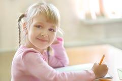 Nette fünf Jahre alte blonde Mädchen, die am Klassenzimmer sitzen Stockbilder