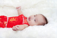 Nette fünf Monate asiatische Baby, die im roten cheongsam lächeln stockfotografie