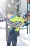 Nette Fahrt des kleinen Jungen auf ein Schwingen im Winter glückliche Kinder, die den Spaß, draußen spielend am Winterweg haben lizenzfreie stockfotografie