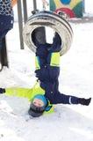 Nette Fahrt des kleinen Jungen auf ein Schwingen im Winter glückliche Kinder, die den Spaß, draußen spielend am Winterweg haben stockfotografie