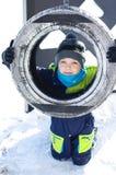 Nette Fahrt des kleinen Jungen auf ein Schwingen im Winter glückliche Kinder, die den Spaß, draußen spielend am Winterweg haben lizenzfreie stockfotos