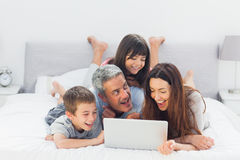 Nette Familie, die auf Bett unter Verwendung ihres Laptops liegt Stockfoto