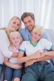 Nette Familie, die auf Couch sitzt lizenzfreie stockfotografie