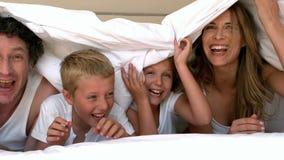 Nette Familie, die auf ihrem Bett sich versteckt stock footage