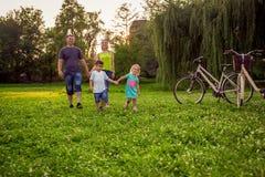 Nette Familie, die in der lustigen Zeit der Natur genießt stockbilder