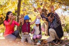 Nette Familie, die mit Herbstlaub spielt stockfotografie