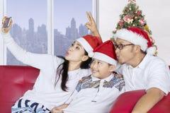 Nette Familie, die selfie mit Sankt-Hut nimmt Lizenzfreies Stockfoto