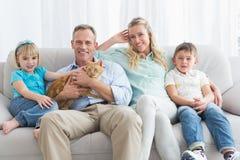 Nette Familie, die sich zusammen auf der Couch mit ihrer Katze entspannt stockfotografie