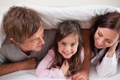 Nette Familie, die unter einem Duvet liegt lizenzfreie stockbilder