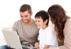 Nette Familie, die zusammen an ihrem Laptop arbeitet Stockfoto