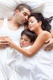 Nette Familie, die zusammen schläft Stockfoto