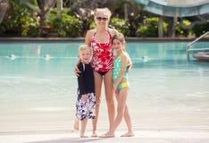 Nette Familie an einem großen Swimmingpool im Freien Stockbild