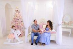 Nette Familie erfasst, um Weihnachtsgeschenke in hellem s auszutauschen Lizenzfreie Stockbilder