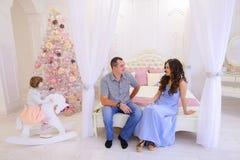 Nette Familie erfasst, um Weihnachtsgeschenke in hellem s auszutauschen Lizenzfreie Stockfotografie