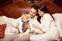 Nette Familie im Schlafzimmer Mutter, Vater und Tochter im i lizenzfreies stockfoto