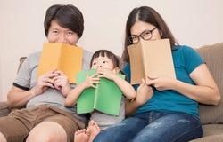 Nette Familienabdeckung ihr Gesicht mit Büchern Stockbilder