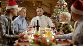 Nette Familienmitglieder, die während des Weihnachtsessens, des unfocus und dann des Fokus sprechen stock video