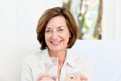 Nette fällige Frau mit Pillen Lizenzfreie Stockfotos