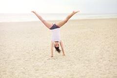 Nette Frau auf dem Strand, der Handstand tut stockfoto