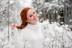 Nette Frau des Ingwers in der weißen Strickjacke im Winterwaldschnee Dezember im Park Porträt Weihnachtsnette Zeit Stockfoto