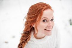 Nette Frau des Ingwers in der weißen Strickjacke im Winterwaldschnee Dezember im Park Porträt Weihnachtsnette Zeit Lizenzfreies Stockfoto
