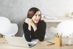 Nette Frau, die am Arbeitsplatz blinzelt Lizenzfreies Stockbild