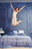 Nette Frau, die auf das Bett mit den ausgestreckten Armen im Bett springt Stockfotografie