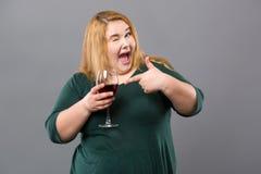 Nette nette Frau, die auf das Glas mit Wein zeigt Lizenzfreie Stockbilder
