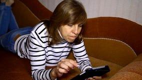 Nette Frau, die auf dem Sofa aufpasst auf die Tablette liegt stock video