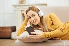 Nette Frau, die auf dem Sofa sich entspannt und Musik hört Stockbilder