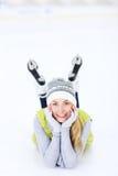 Nette Frau, die auf einer Eisbahn liegt lizenzfreie stockbilder
