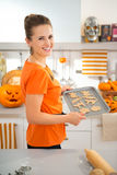 Nette Frau, die Behälter von ungekochten Halloween-Keksen hält Stockbilder