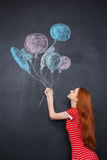 Nette Frau, die bunte Ballone gezeichnet auf Tafelhintergrund hält Stockbild
