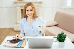 Nette Frau, die eine Tasse Tee beim Arbeiten hält Lizenzfreies Stockbild