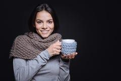 Nette Frau, die eine Tasse Tee im Studio hält Stockbild