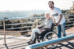 Nette nette Frau, die in einem Rollstuhl sitzt Lizenzfreie Stockbilder