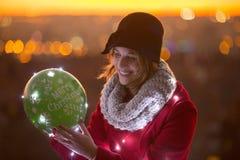 Nette Frau, die einen Ballon mit geführten Lichtern im Winter hält Stockfoto