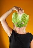 Nette Frau, die einen Kohl als Maske hält Lizenzfreies Stockfoto