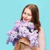 Nette Frau, die Geruch von lila Blumen des Blumenstraußes über blauem Hintergrund genießt Lizenzfreies Stockfoto