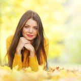 Nette Frau, die in Herbstpark legt Stockbilder