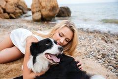 Nette Frau, die ihren Hund auf dem Strand im Sommer umarmt Lizenzfreies Stockbild