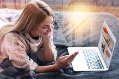 Nette nette Frau, die ihren Smartphoneschirm betrachtet Lizenzfreie Stockfotografie