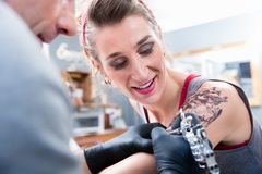 Nette Frau, die im Vertrauen in einem modernen Tätowierungsstudio lächelt Lizenzfreies Stockfoto