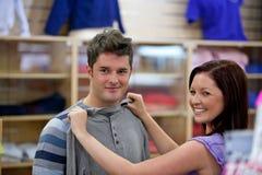 Nette Frau, die Kleidung für ihren Freund wählt Lizenzfreies Stockfoto